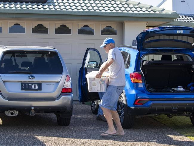 Paul Dawson moves items into his daughter's house at Biggera Waters on the Gold Coast. Picture: Glenn Hunt.