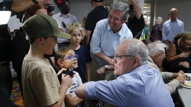 Prime Minister Scott Morrison chats to children at the Club Taree Evacuation Centre. Picture: AAP