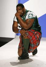 "NFL New York Jets player Damien Woody presents a creation during a ""Dressed To Kilt"" fashion event in New York."