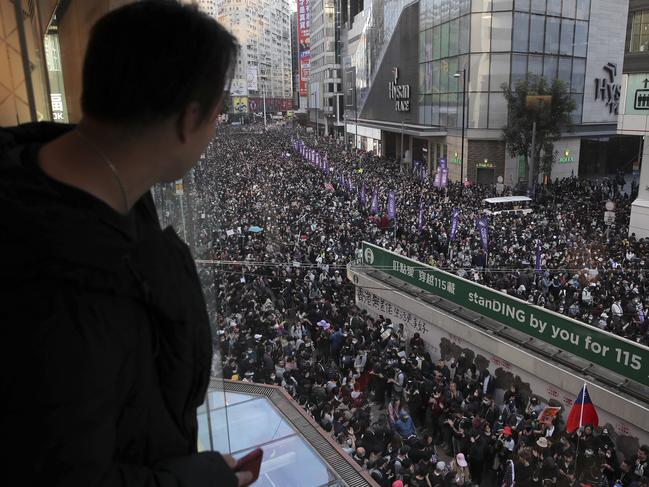 A man watches pro-democracy protesters march on a street during a protests in Hong Kong. Picture: AP