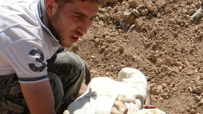 A man carries the body of a child into a mass grave following the attacks. Picture: AFP
