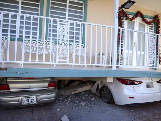 Cars are crushed under a home that collapsed after an earthquake hit Guanica, Puerto Rico, on Monday. Picture: AP