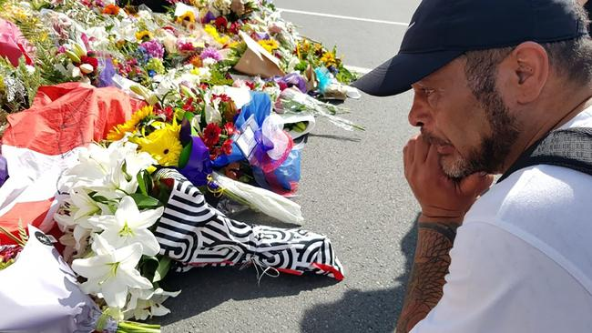 A resident gets emotional as he pays his respect by placing flowers for the victims of the mosques attacks in Christchurch. Picture: Glenda KWEK / AFP.