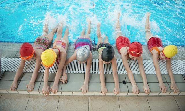 happy children kids group at swimming pool class learning to swim.