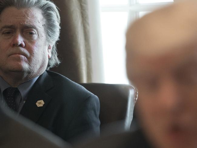 Bannon listens as Donald Trump speaks to the press in the Cabinet Room of the White House. Picture: AFP
