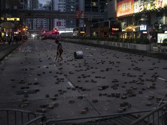 A woman walks past bricks thrown by protesters. Picture: AP
