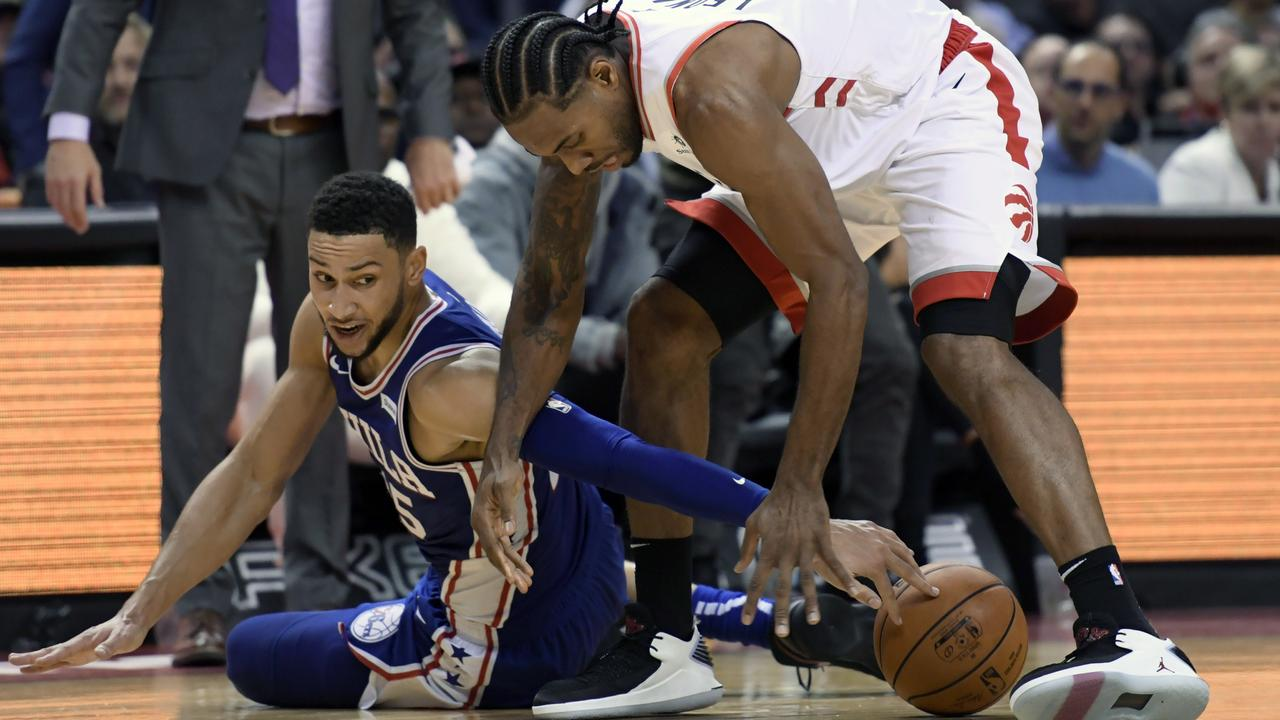 Toronto Raptors forward CJ Miles, right, and Philadelphia 76ers guard Ben Simmons (25) battle for the ball. Picture: The Canadian Press via AP