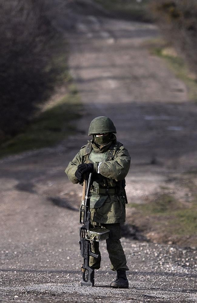 Guarded peace ... An armed man, believed to be a Russian serviceman, stands guard outside a Ukrainian military base in Perevalnoye in Crimea. Picture: Dimitar Dilkoff