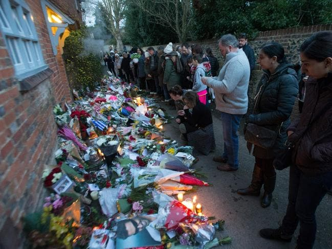 People gather outside the home of British singer George Michael where tributes of flowers, messages and candles have been piled in the village of Goring, southern England. Picture: AFP