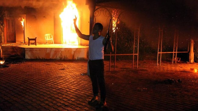 An armed man stands next to the buildings set on fire at the US consulate, on this day in 2012.