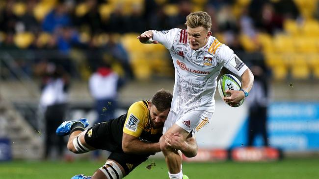 Damian McKenzie of the Chiefs is tackled by Callum Gibbins of the Hurricanes.