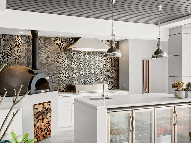 There is an outside kitchen with feature mosaic tiled wall.