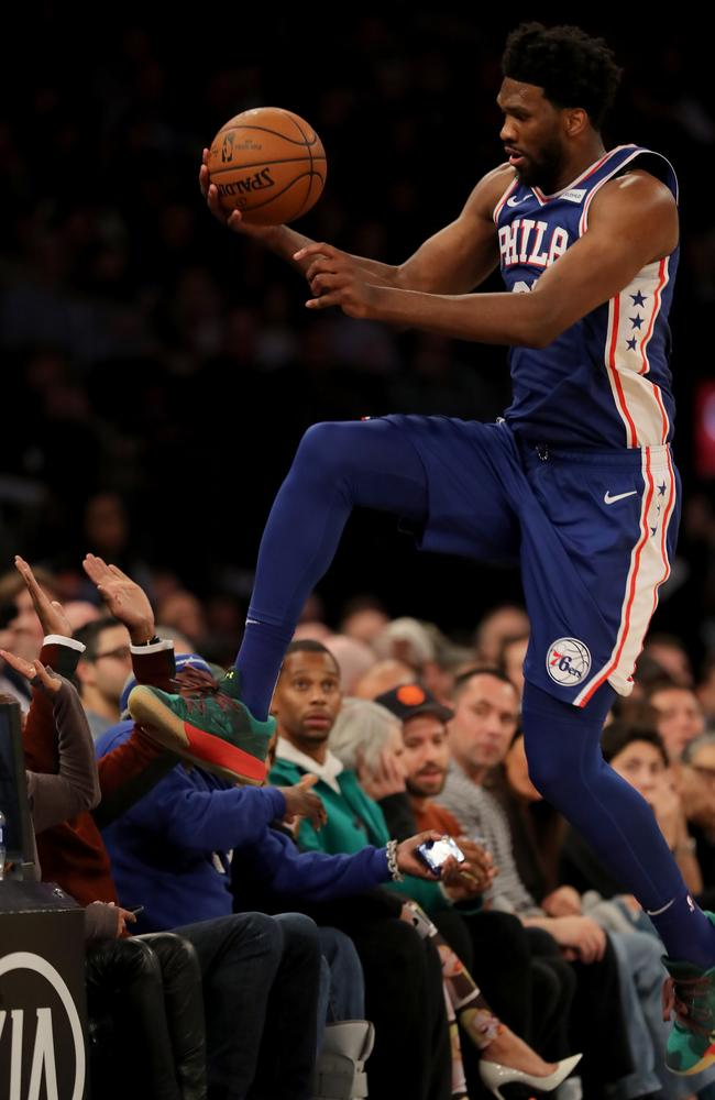 Joel Embiid of the Philadelphia 76ers leaps over the first row in attempt to keep the ball in bounds, leaping over the head of actress Regina King. Picture: Elsa/Getty Images