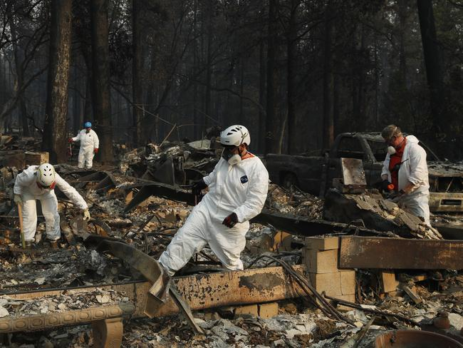 Search and rescue personnel search a home for human remains in the aftermath of the Camp fire in Paradise. Picture: AP