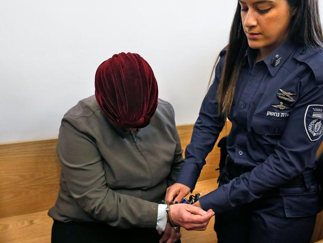 An Israeli policewoman removes handcuffs from Malka Leifer, a former Australian teacher accused of dozens of cases of sexual abuse of girls at a school, as she arrives for a hearing at the District Court in Jerusalem. Picture: Ahmad Gharabli