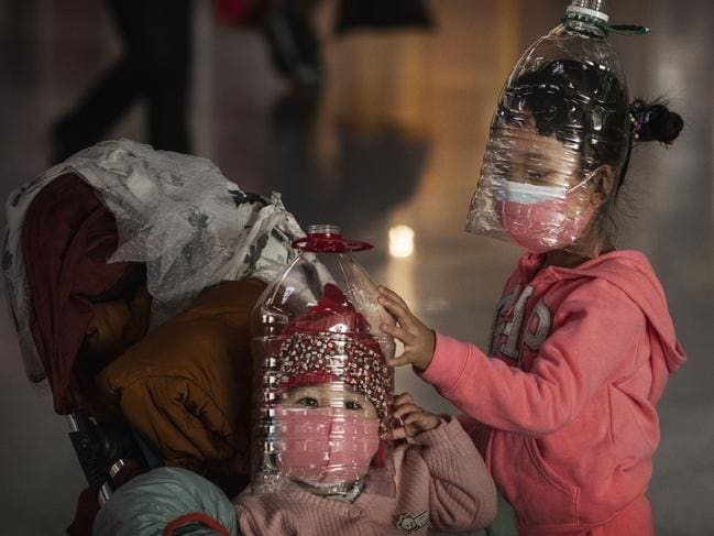 With no idea where the virus came from, people have gone to extreme measures to protect themselves and their children. These children have even taken to wearing plastic bottles as makeshift homemade protective masks in Beijing. Picture: Kevin Frayer/Getty Images.