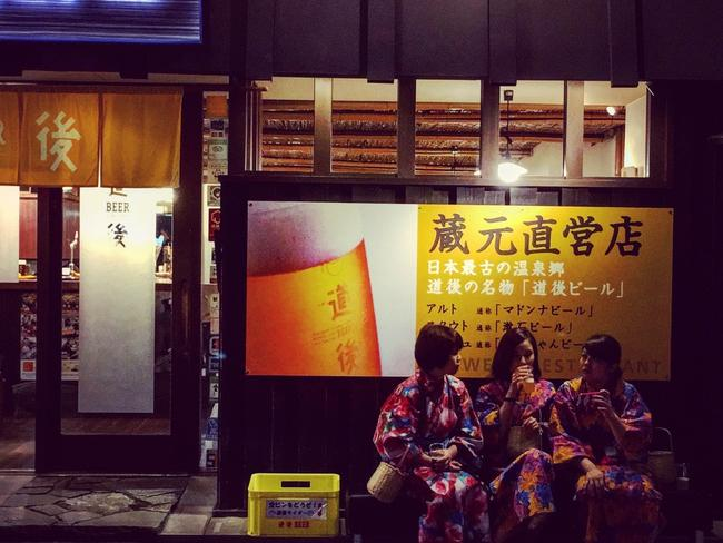 Spa-goers in Dogo Onsen wearing their yukata and carrying their bags of soap and towels. Picture: Paul Ewart