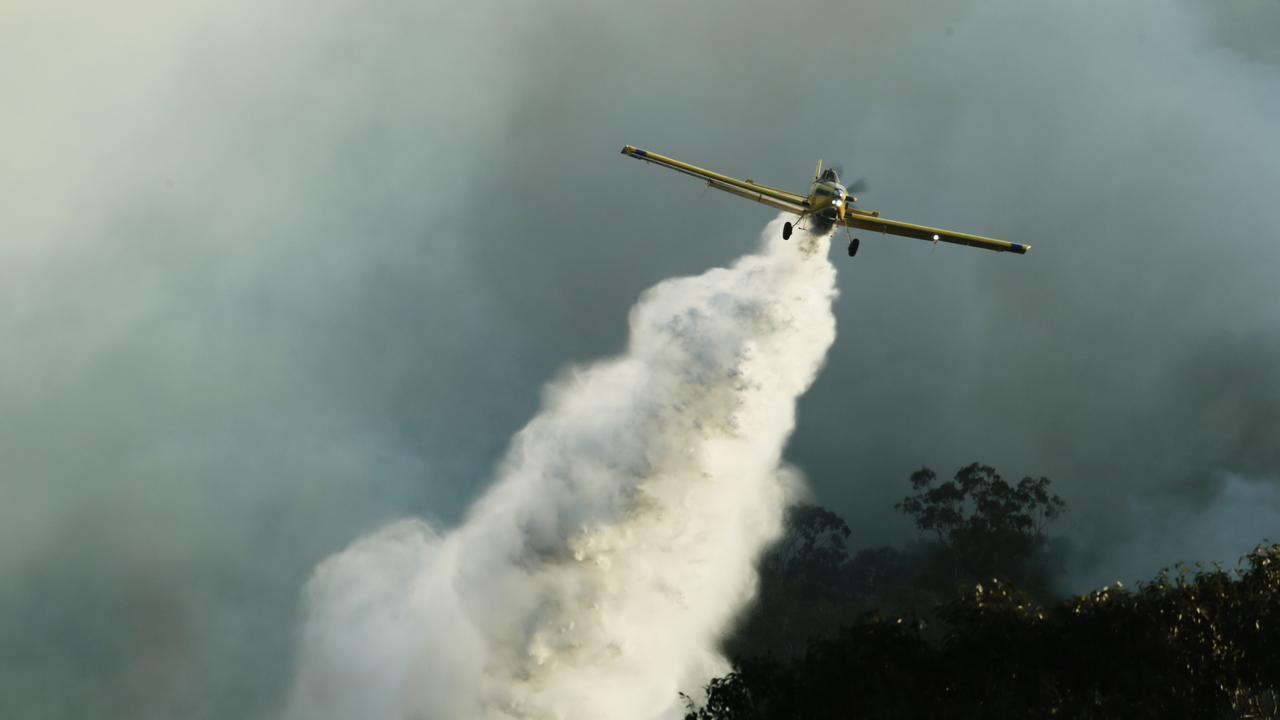 Waterbombers work to save properties along Arcoona Rd in Yandina Creek as bushfires spread across the Sunshine Coast. Picture: Lachie Millard