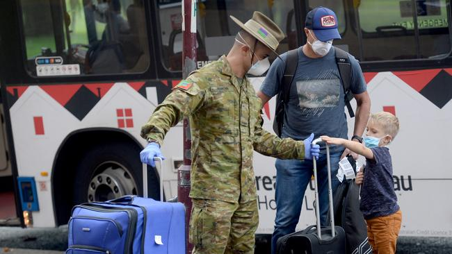 Returning overseas travellers are ushered into the Intercontinental Hotel in Sydney for their 14-day quarantine on Sunday. Picture Jeremy Piper/AAP