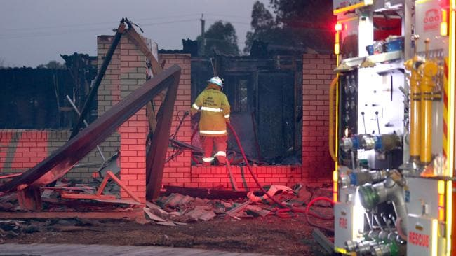 A firefighter at a home destroyed by fire in the Lockyer Valley yesterday. Picture: Steve Pohlner