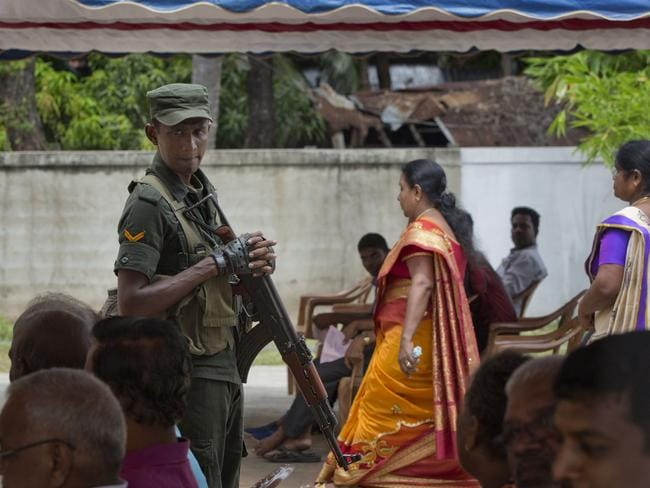 A soldier stands guard amid Catholics attending Mass outside St. Joseph's church in Thannamunai. Picture: AP