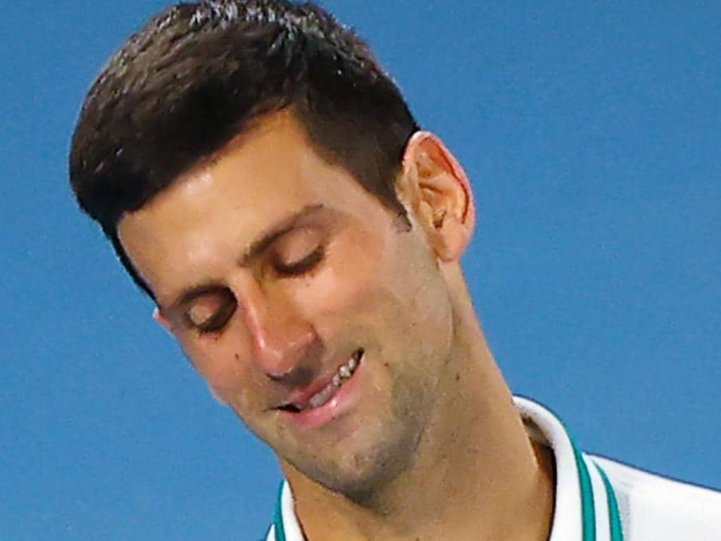 Serbia's Novak Djokovic reacts as he plays against Russia's Daniil Medvedev during their men's singles final match on day fourteen of the Australian Open tennis tournament in Melbourne on February 21, 2021. (Photo by Brandon MALONE / AFP) / -- IMAGE RESTRICTED TO EDITORIAL USE - STRICTLY NO COMMERCIAL USE --