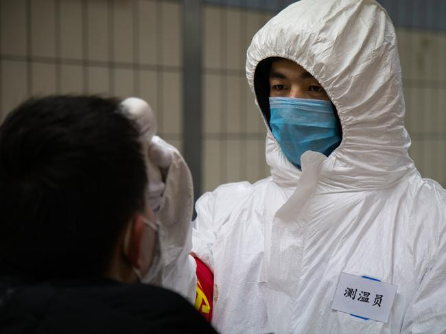 A health worker checks the temperature of a man entering the subway in Beijing, China. Picture: Betsy Joles/Getty Images