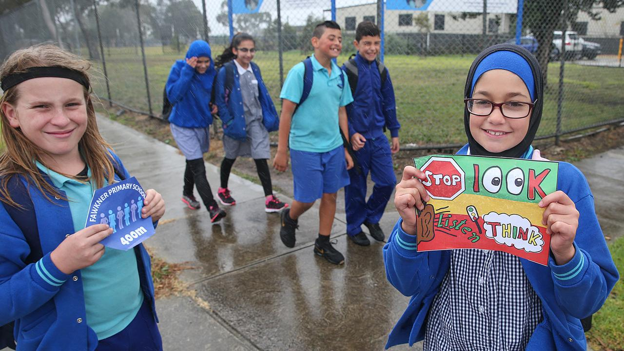 Grade 6 students Jude and Alinar holding their designs for the walk as Aya, Faliha, Logan and Zein from Fawkner Primary School walk to school. Picture: Ian Currie