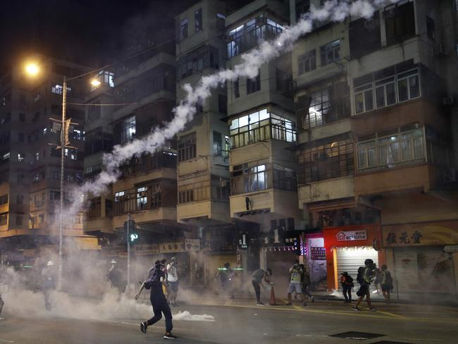 Protesters react to teargas from Shum Shui Po police station in Hong Kong on Wednesday. Picture: AP