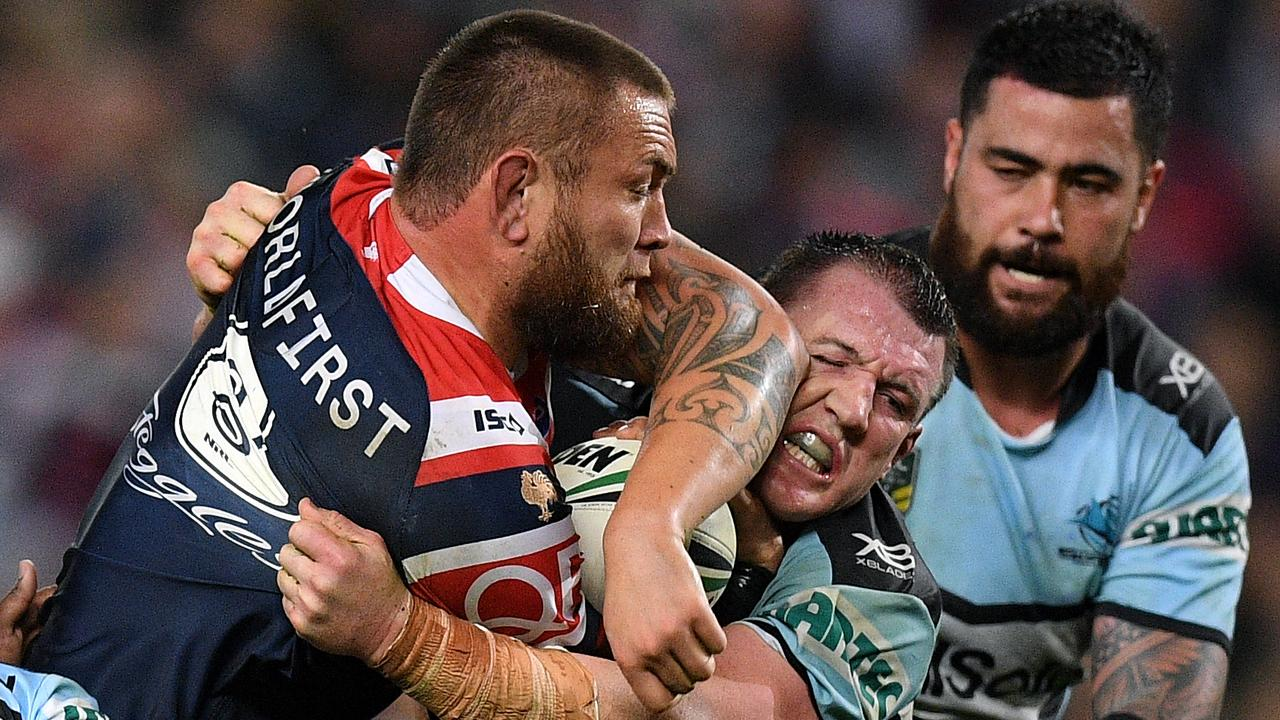 Jared Waerea-Hargreaves of the Roosters is tackled by of the Sharks
