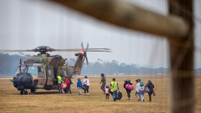 Evacuees board a Royal Australian Navy MRH-90 helicopter at Mallacoota. Picture: AFP