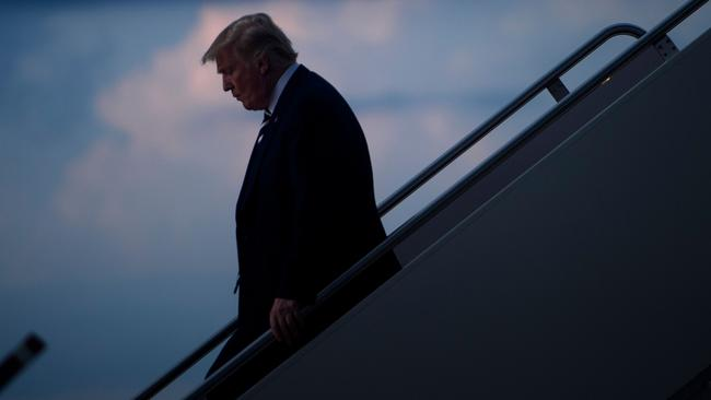 Mr Trump strikes a lonely figure as he disembarks from Air Force One. Picture: Brendan Smialowski/AFP