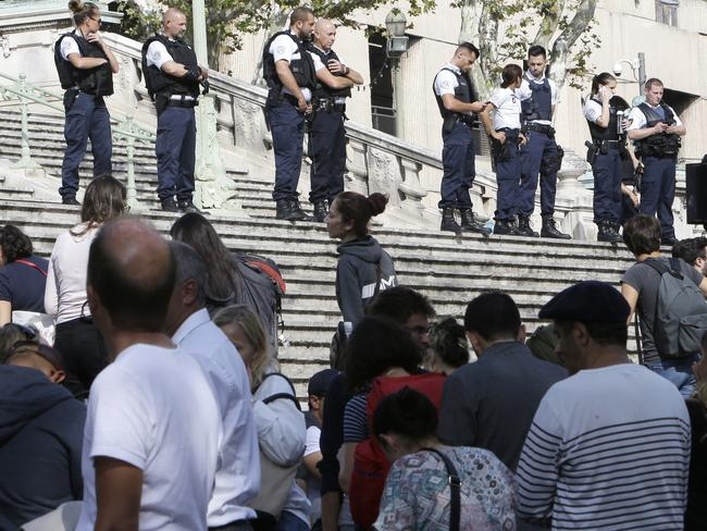 Passengers wait in front a line a police officers blocking the access to Marseille's main train station. Picture: AP Photo/Claude Paris