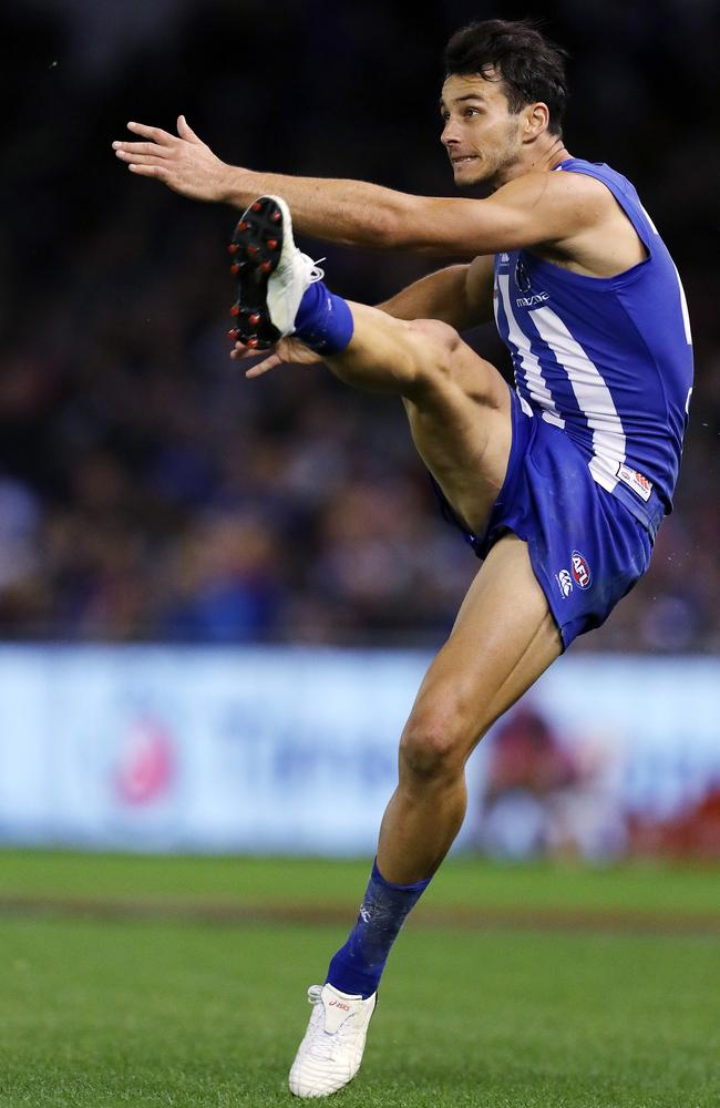 North Melbourne's Robbie Tarrant gets a kick away against the Dogs.