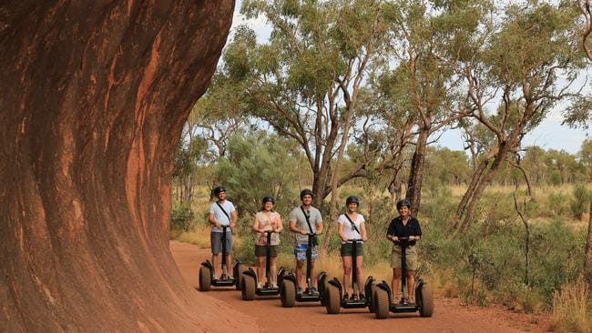 Visitors can travel around the base of Uluru by segway. Picture: Voyages Indigenous Tourism Australia