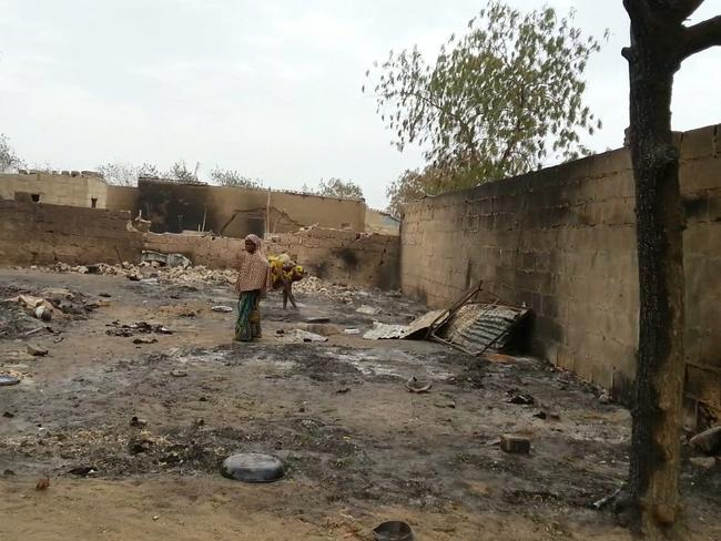 A young girl stands amid the burned ruins of Baga, Nigeria. Hundreds of bodies — too many to count — remain strewn in the bush. Picture: Umar