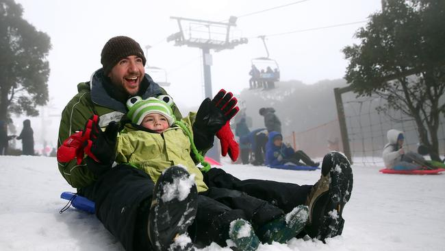 Craig and Cooper Hecht snow play on the toboggan on in Mount Buller. Picture: Getty