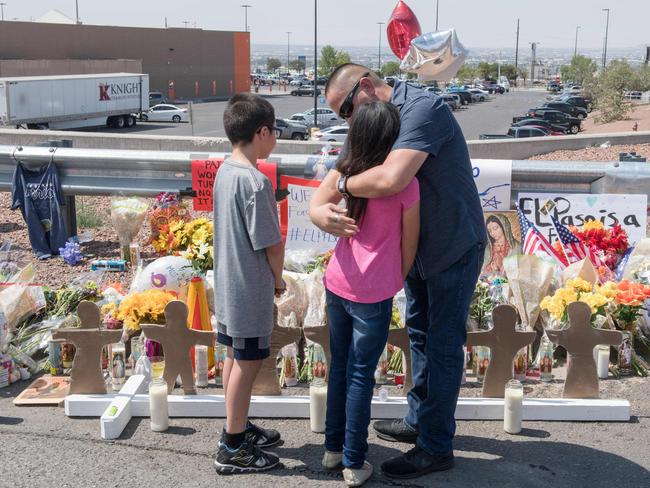 Members of the Soto family embrace beside a makeshift memorial after the shooting that left 22 people dead at the Cielo Vista Mall WalMart in El Paso, Texas. Picture: AFP