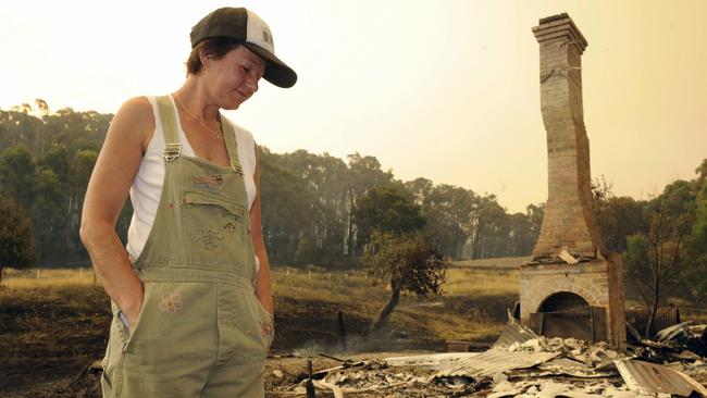 Boolarra resident Pam Warren among the remains of her neighbour's house after bushfires devastated the town.