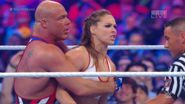 Ronda Rousey is held back by Kurt Angle after a Stephanie McMahon cheap shot.