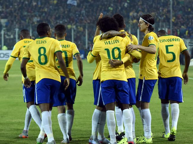 Brazil's forward Roberto Firmino celebrates with teammates after scoring against Venezuela.
