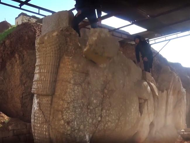 IS militants destroy winged-bull Assyrian protective deity in the Ninevah Museum in Mosul, Iraq. AP Photo via militant social media account.