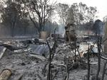 The ruins of a house smoulders on Old Bar road Near Taree, NSW, Saturday, November 9, 2019. Two people have been killed and seven others are missing in bushfires in NSW which have also destroyed at least 100 homes. (AAP Image/Darren Pateman)