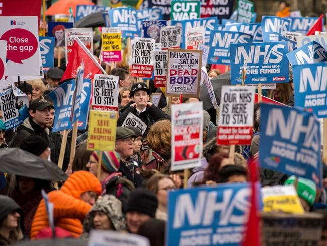 Demonstrators carry placards during a People's Assembly demonstration against the Conservative government's health policy in London, England. Picture: Getty Images