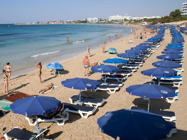 Tourists sunbath at the beach in the resort town of Ayia Napa in southeastern Cyprus. Picture: Florian Choblet