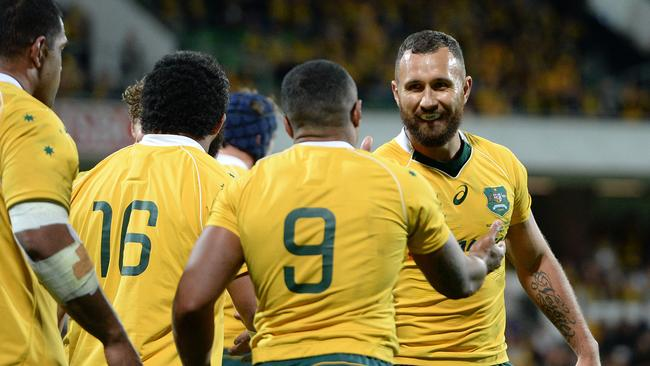 Former Wallabies star Quade Cooper congratulates Will Genia after scoring a try.