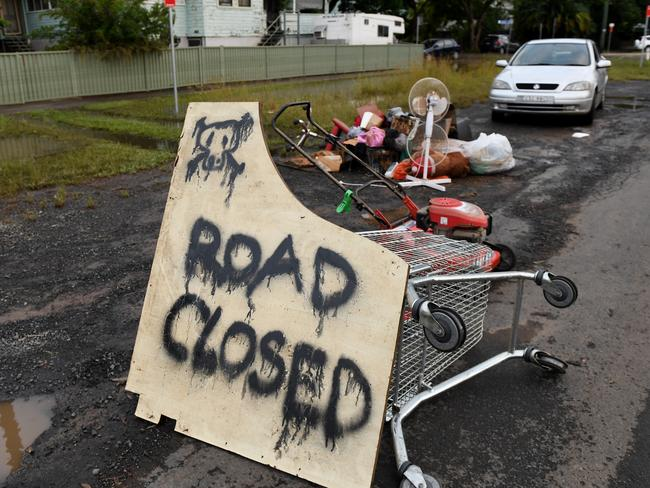 Residents fed up with people looking at the flooding erect 'Road Closed' signs on their street and create barricades out of debris as floodwaters recede in Lismore. Picture: AAP/Tracey Nearmy