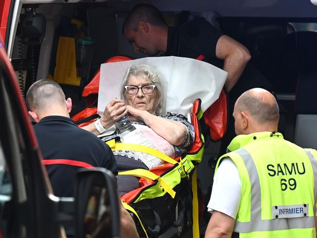 Emergency workers stretcher a woman to a waiting ambulance after a suspected package bomb blast along a pedestrian street in the heart of Lyon. Picture: AFP
