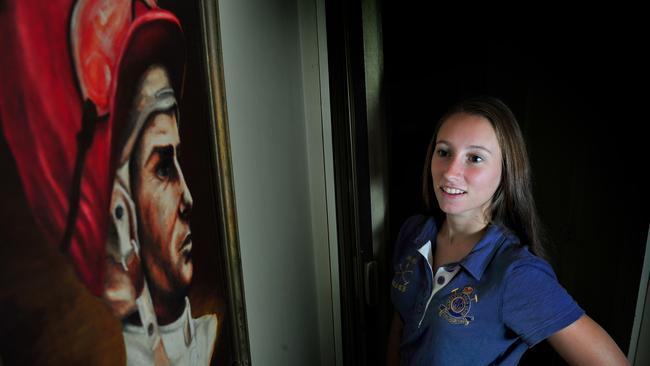 Katelyn Mallyon admires a painting of her grandfather, legendary jockey Mick Mallyon.