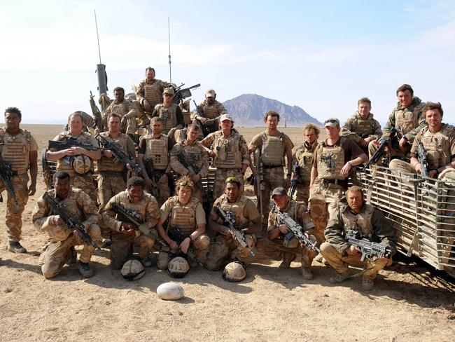 Prince Harry (5th right) poses with soldiers in the desert on February 19, 2008 in Helmand Province, Afghanistan. Picture: John Stillwell